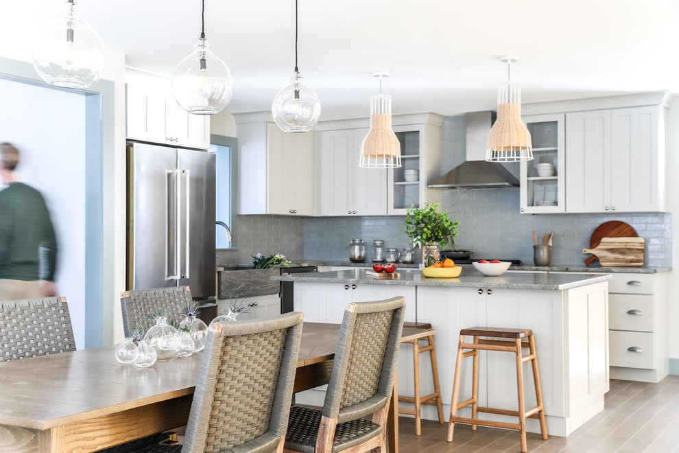 Open concept kitchen - mid-sized coastal l-shaped medium tone wood floor open concept kitchen idea in Portland Maine with an integrated sink, shaker cabinets, gray cabinets, granite countertops, blue backsplash, brick backsplash, stainless steel appliances, an island and gray countertops