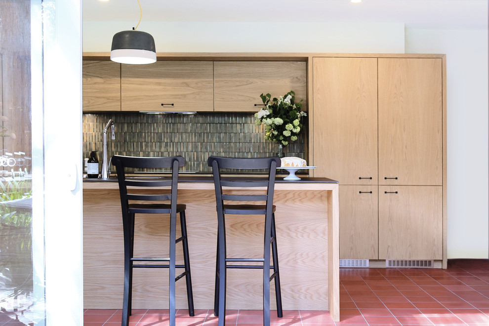 Inspiration for a mid-sized modern u-shaped terra-cotta tile eat-in kitchen remodel in Melbourne with an undermount sink, flat-panel cabinets, light wood cabinets, solid surface countertops, multicolored backsplash, mosaic tile backsplash, stainless steel appliances and an island
