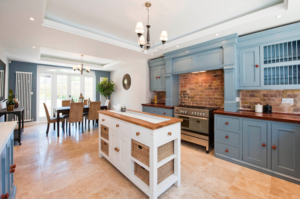 Eat-in kitchen - victorian eat-in kitchen idea in London with recessed-panel cabinets, blue cabinets and wood countertops