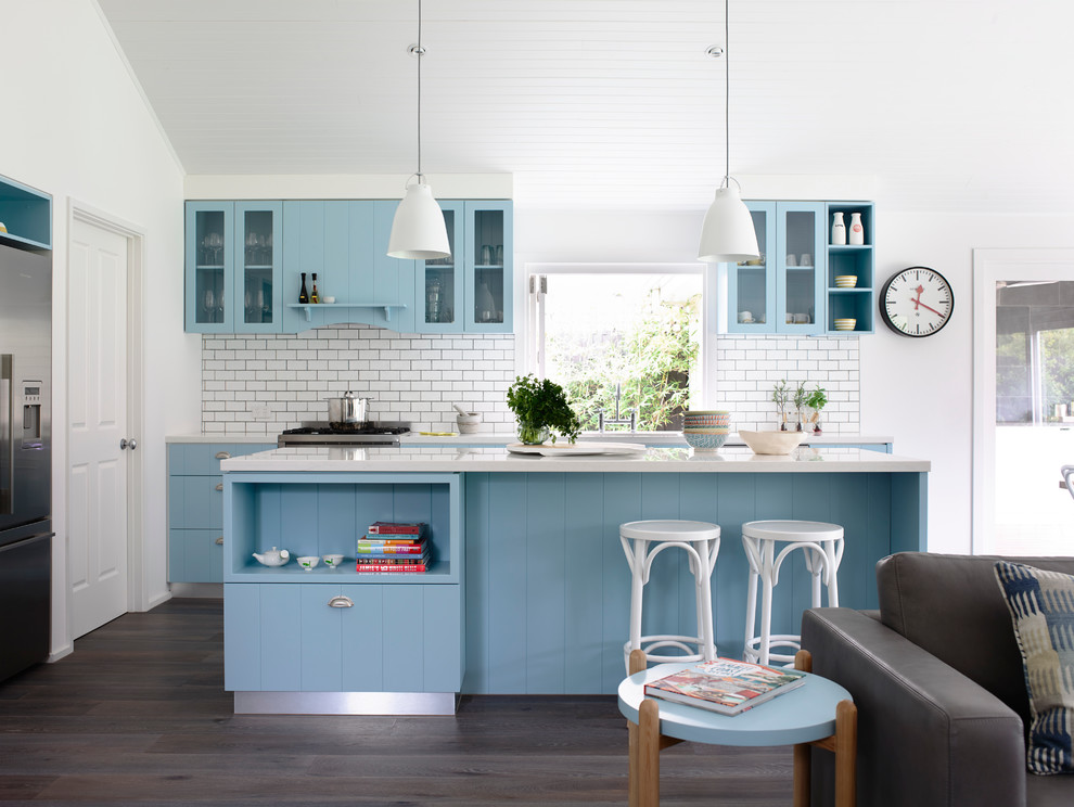 Example of a coastal single-wall open concept kitchen design in Melbourne with blue cabinets, quartz countertops, white backsplash, subway tile backsplash, stainless steel appliances, flat-panel cabinets and an island