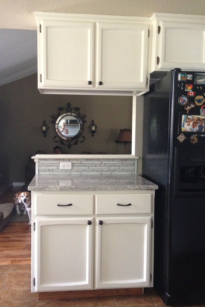 Small beach style u-shaped ceramic tile eat-in kitchen photo in Sacramento with recessed-panel cabinets, white cabinets, granite countertops, gray backsplash, glass sheet backsplash, stainless steel appliances and an undermount sink