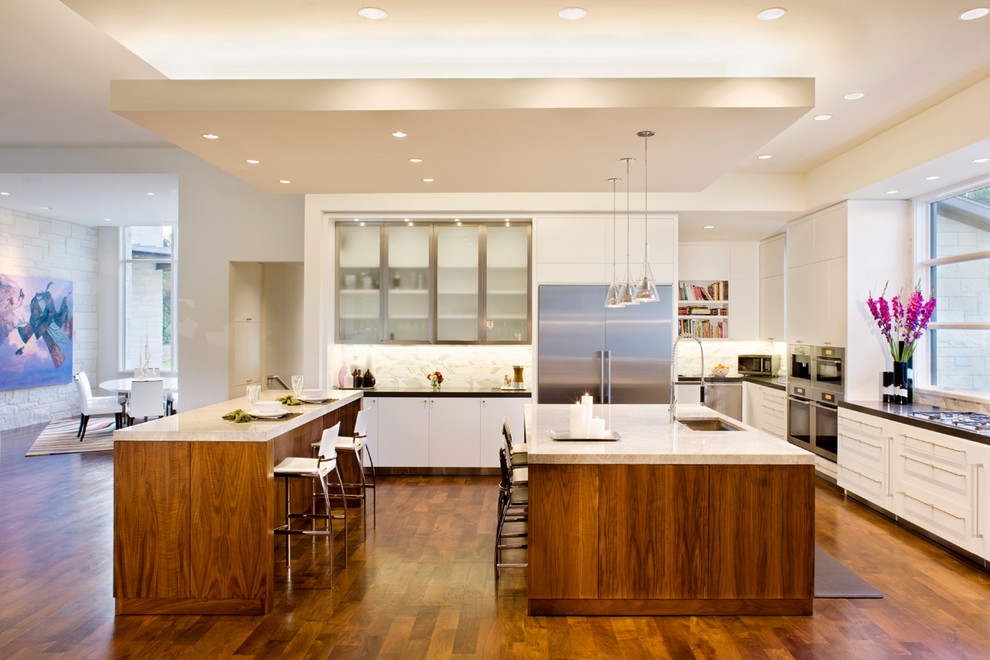 Example of a trendy galley dark wood floor open concept kitchen design in Austin with white cabinets, flat-panel cabinets, white backsplash, stone tile backsplash, stainless steel appliances, two islands and an undermount sink