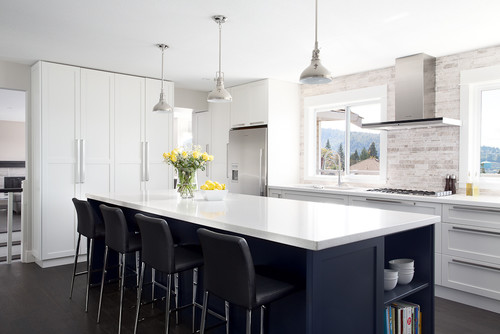A bright white kitchen design with a dark indigo blue kitchen island and solid white countertops.