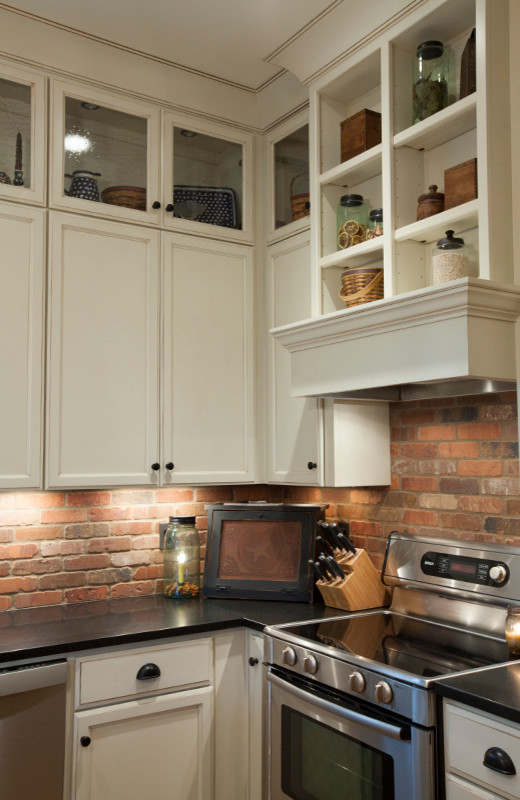 Eat-in kitchen - small craftsman l-shaped eat-in kitchen idea in Louisville with recessed-panel cabinets, white cabinets, brown backsplash, stainless steel appliances and an island