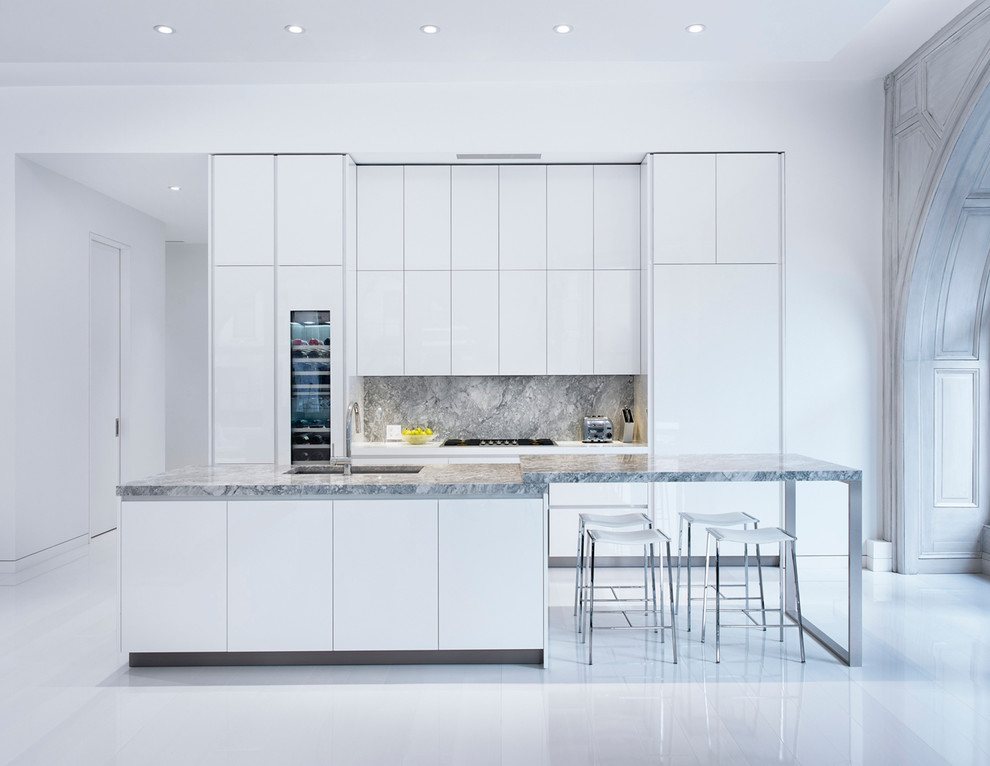 Inspiration for a scandinavian galley kitchen remodel in New York with an undermount sink, flat-panel cabinets, white cabinets, gray backsplash, paneled appliances and an island