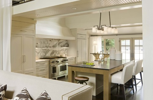 In this kitchen remodel, marble is used on the entire wall behind the stove and above the countertop.