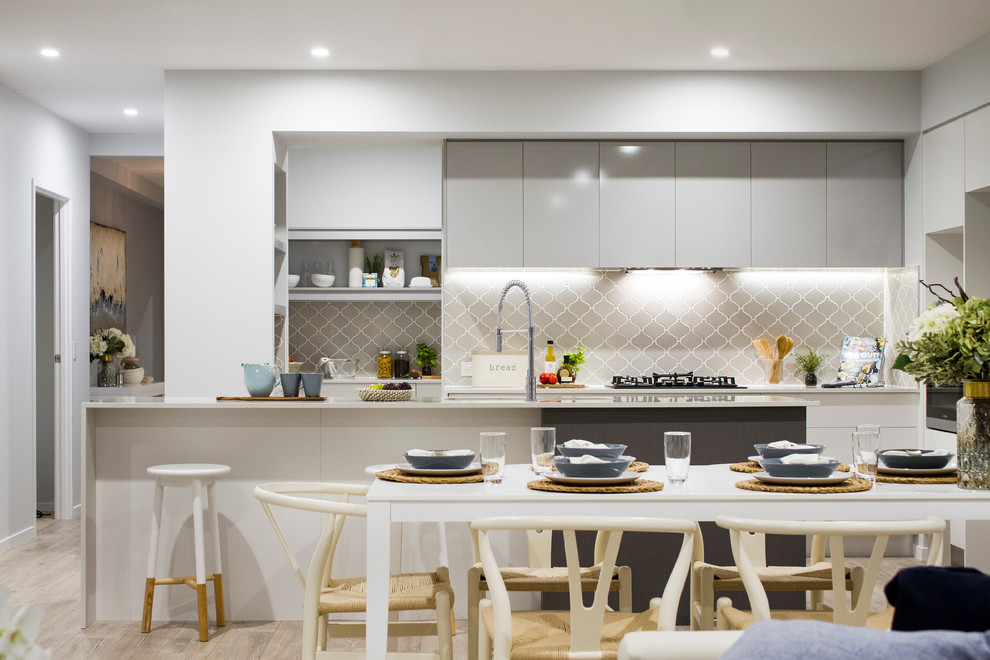 Inspiration for a coastal galley open concept kitchen remodel in Brisbane with flat-panel cabinets, gray cabinets, gray backsplash and a peninsula