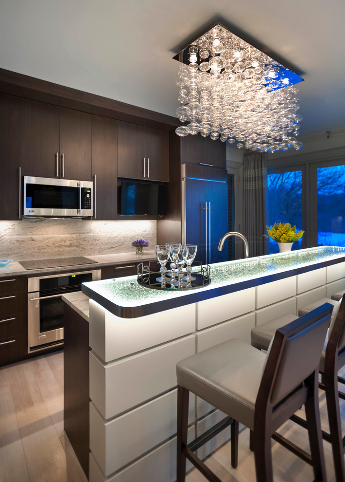 Inspiration for a large contemporary galley porcelain tile kitchen remodel in Detroit with flat-panel cabinets, stainless steel appliances, glass countertops, a single-bowl sink, dark wood cabinets, brown backsplash, stone slab backsplash and an island