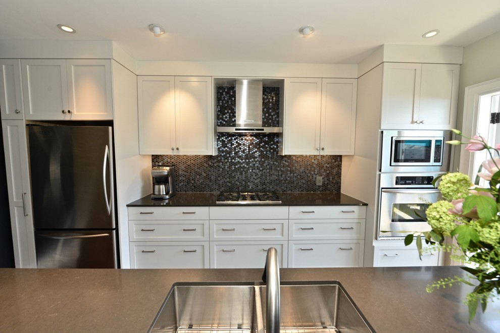 Inspiration for a mid-sized contemporary galley dark wood floor and brown floor eat-in kitchen remodel in Toronto with an undermount sink, shaker cabinets, white cabinets, solid surface countertops, gray backsplash, glass tile backsplash, stainless steel appliances, an island and gray countertops