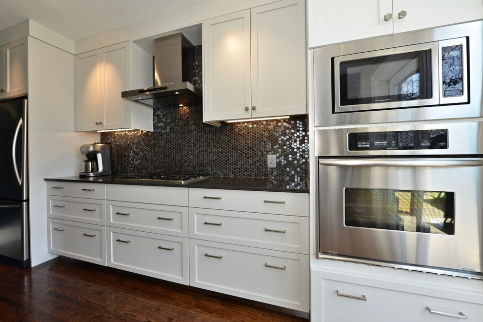 Example of a mid-sized trendy galley dark wood floor and brown floor eat-in kitchen design in Toronto with an undermount sink, shaker cabinets, white cabinets, solid surface countertops, gray backsplash, glass tile backsplash, stainless steel appliances, an island and gray countertops