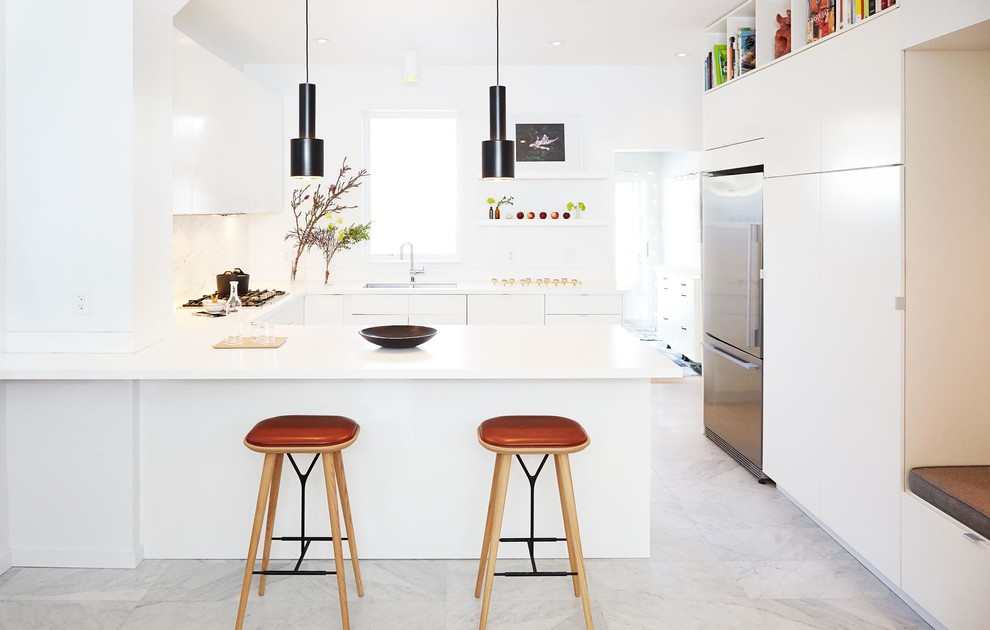 Kitchen - mid-sized modern u-shaped marble floor and gray floor kitchen idea in Toronto with flat-panel cabinets, white cabinets, solid surface countertops, stainless steel appliances, a double-bowl sink, white backsplash, marble backsplash and a peninsula