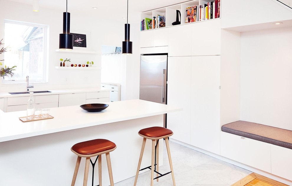 Inspiration for a mid-sized modern u-shaped marble floor open concept kitchen remodel in Toronto with an undermount sink, flat-panel cabinets, white cabinets, solid surface countertops, gray backsplash, stone slab backsplash and stainless steel appliances