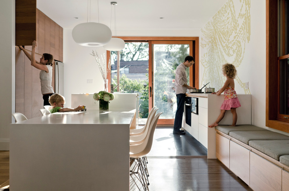 Eat-in kitchen - modern eat-in kitchen idea in Toronto with stainless steel appliances, flat-panel cabinets and dark wood cabinets