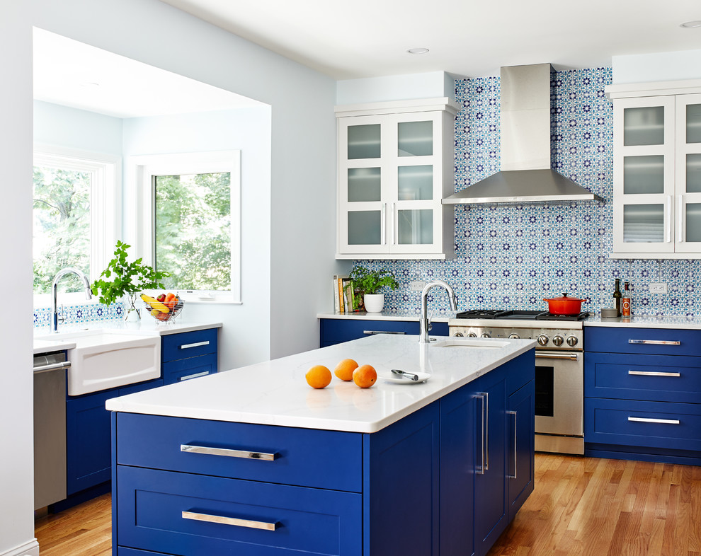Transitional light wood floor kitchen photo in DC Metro with a farmhouse sink, shaker cabinets, blue cabinets, multicolored backsplash, stainless steel appliances, an island and white countertops