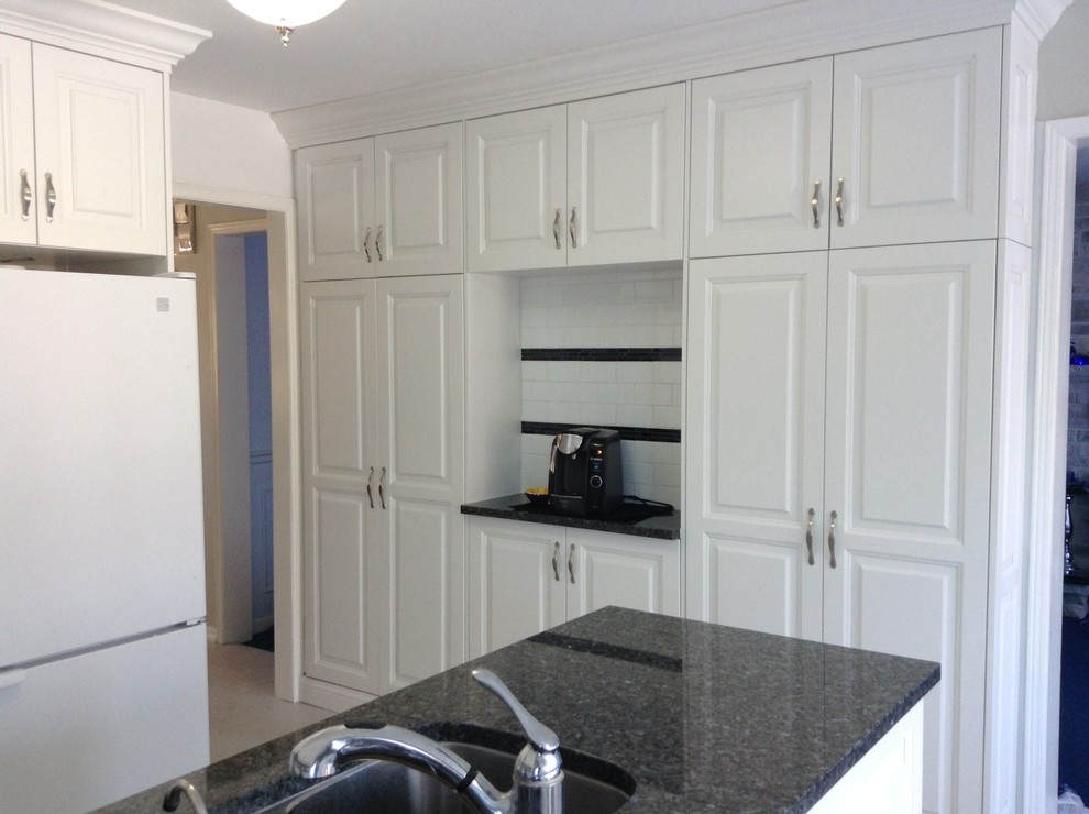 Kitchen pantry - kitchen pantry idea in Other with raised-panel cabinets, white cabinets, granite countertops and white backsplash