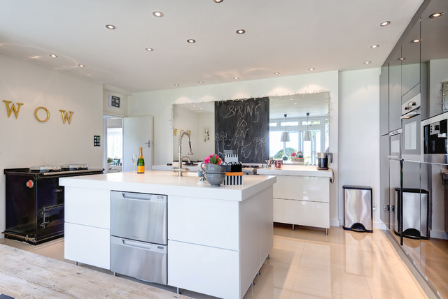 Contemporary kitchen in Devon with flat-panel cabinets, white cabinets and black appliances.