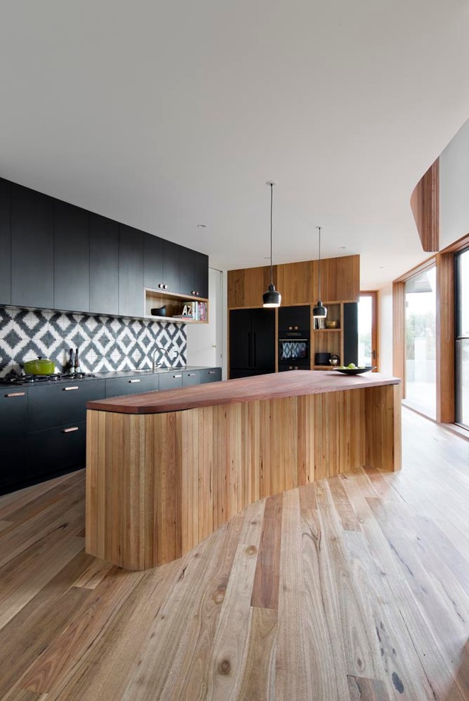 Kitchen - mid-sized contemporary medium tone wood floor kitchen idea in Melbourne with flat-panel cabinets, black cabinets, wood countertops, multicolored backsplash, cement tile backsplash, black appliances and an island