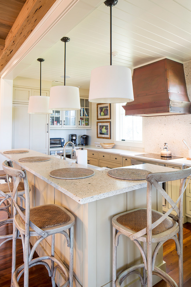 Example of a cottage u-shaped kitchen design in Philadelphia with recessed-panel cabinets and an island