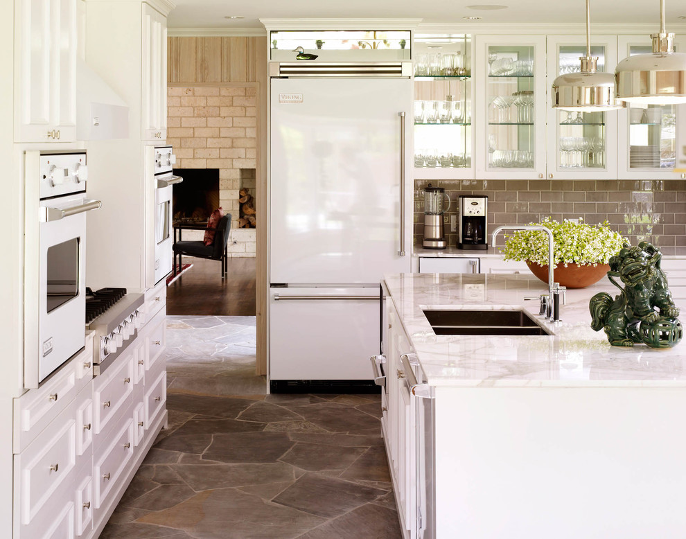 Example of a classic slate floor kitchen design in Dallas with a double-bowl sink, glass-front cabinets, white cabinets, gray backsplash, subway tile backsplash and white appliances