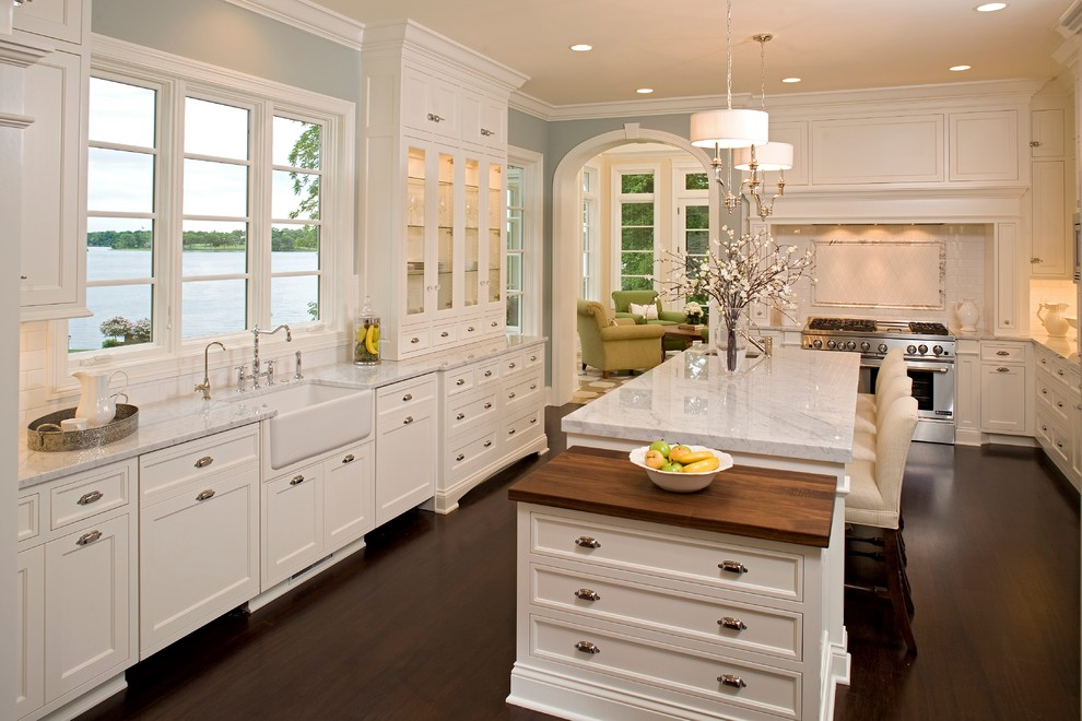 Inspiration for a large timeless u-shaped dark wood floor and brown floor enclosed kitchen remodel in Minneapolis with a farmhouse sink, marble countertops, white cabinets, white backsplash, subway tile backsplash, stainless steel appliances, an island, white countertops and recessed-panel cabinets