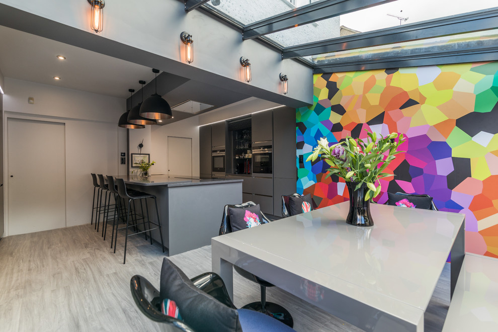 Example of a mid-sized trendy galley gray floor and light wood floor eat-in kitchen design in London with flat-panel cabinets, gray cabinets, an island and stainless steel appliances