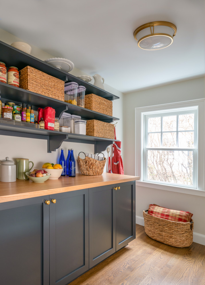 Inspiration for a mid-sized timeless medium tone wood floor kitchen pantry remodel in Boston with raised-panel cabinets, wood countertops and brown countertops