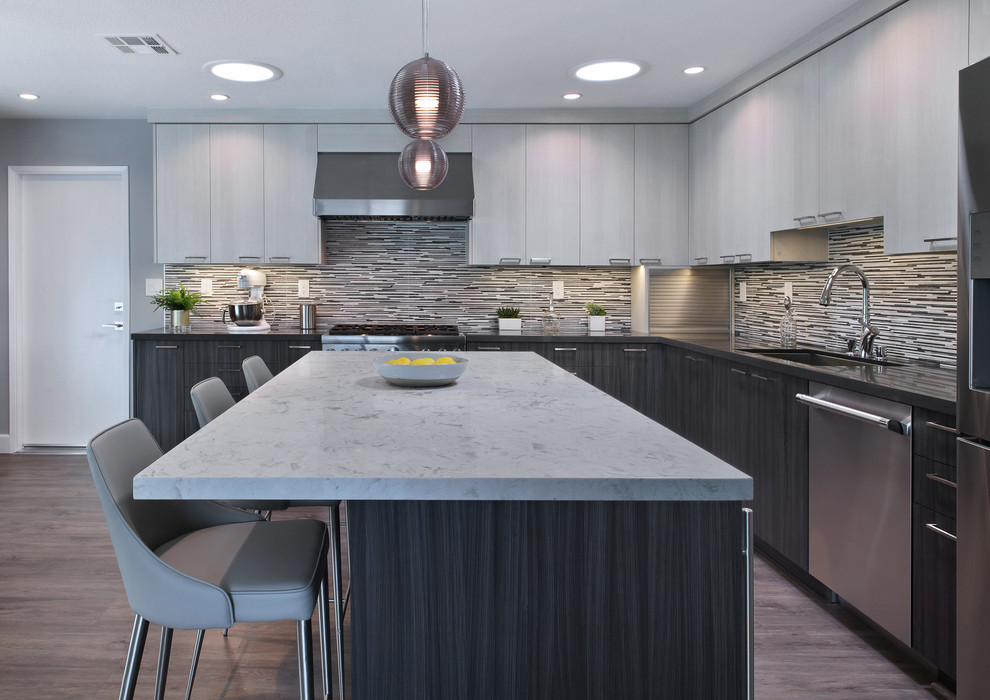 Inspiration for a mid-sized contemporary l-shaped gray floor and laminate floor eat-in kitchen remodel in Orange County with flat-panel cabinets, gray cabinets, porcelain backsplash, stainless steel appliances, an island, a drop-in sink, quartz countertops and multicolored backsplash