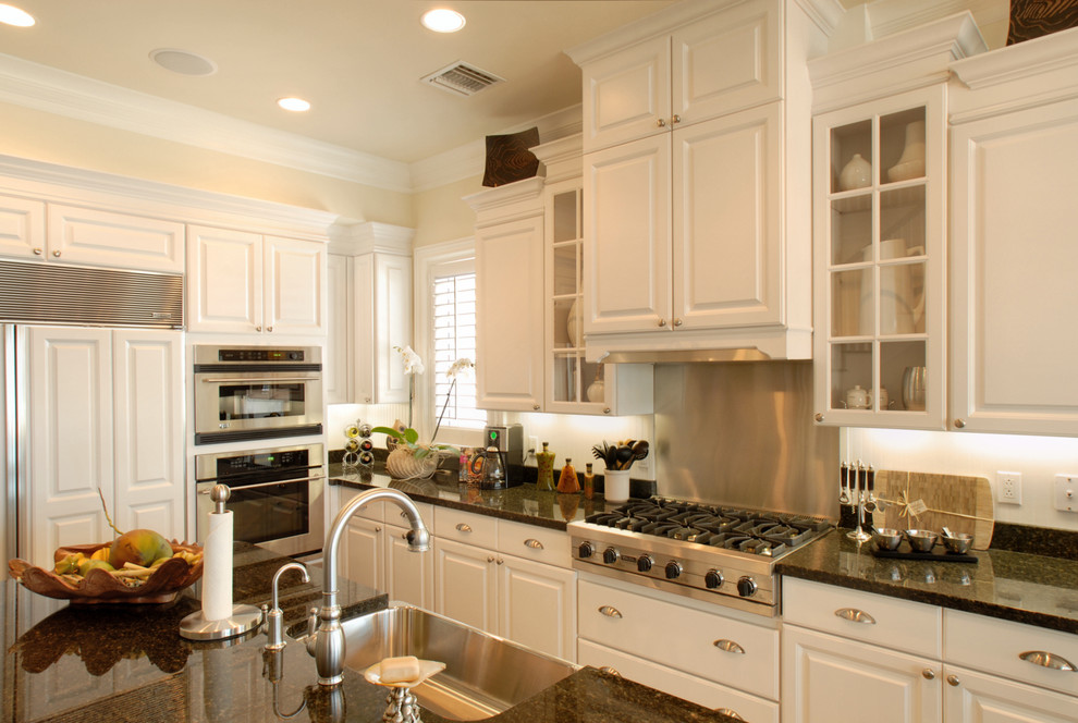 Large elegant kitchen photo in Miami with paneled appliances, granite countertops, a farmhouse sink, raised-panel cabinets and white cabinets