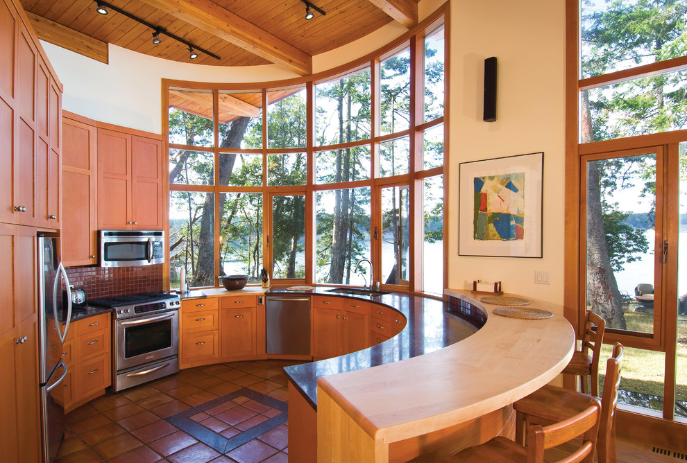 Example of a trendy u-shaped terra-cotta tile and orange floor open concept kitchen design in Vancouver with an undermount sink, shaker cabinets, medium tone wood cabinets, red backsplash, mosaic tile backsplash, stainless steel appliances and a peninsula