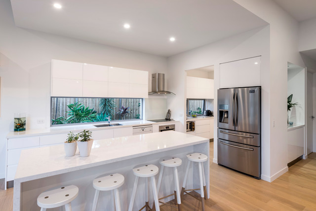 Inspiration for a mid-sized tropical galley open plan kitchen in Gold Coast - Tweed with a double-bowl sink, flat-panel cabinets, white cabinets, quartz benchtops, white splashback, glass sheet splashback, stainless steel appliances, light hardwood floors, an island, brown floor and white benchtop.