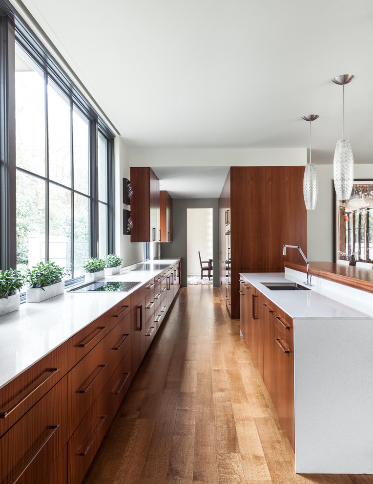 Inspiration for a modern galley kitchen remodel in Dallas with an undermount sink, flat-panel cabinets and medium tone wood cabinets