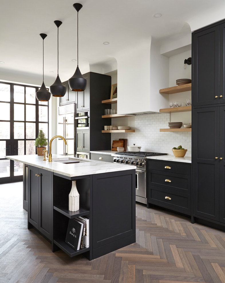 Example of a transitional medium tone wood floor kitchen design in Toronto with an undermount sink, shaker cabinets, black cabinets, white backsplash, subway tile backsplash, stainless steel appliances and an island