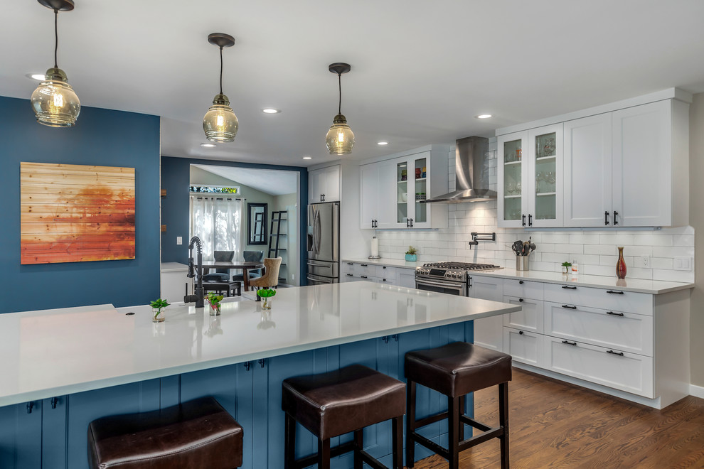 Eat-in kitchen - large transitional l-shaped dark wood floor and brown floor eat-in kitchen idea in Portland with a farmhouse sink, recessed-panel cabinets, quartz countertops, white backsplash, subway tile backsplash, stainless steel appliances, an island and white countertops