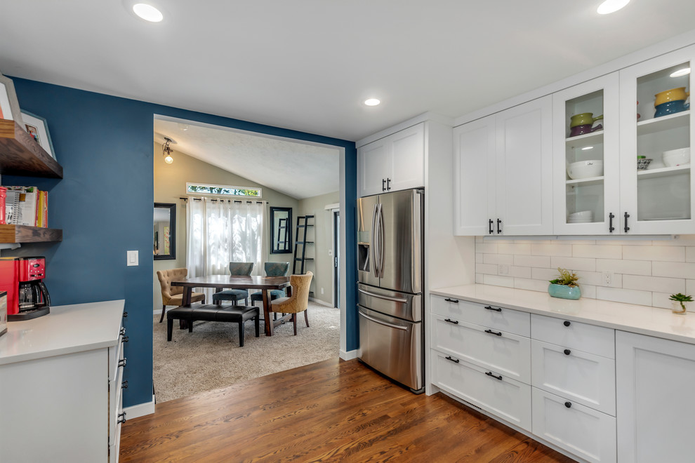 Example of a large transitional l-shaped dark wood floor and brown floor eat-in kitchen design in Portland with a farmhouse sink, recessed-panel cabinets, white cabinets, quartz countertops, white backsplash, subway tile backsplash, stainless steel appliances, an island and white countertops