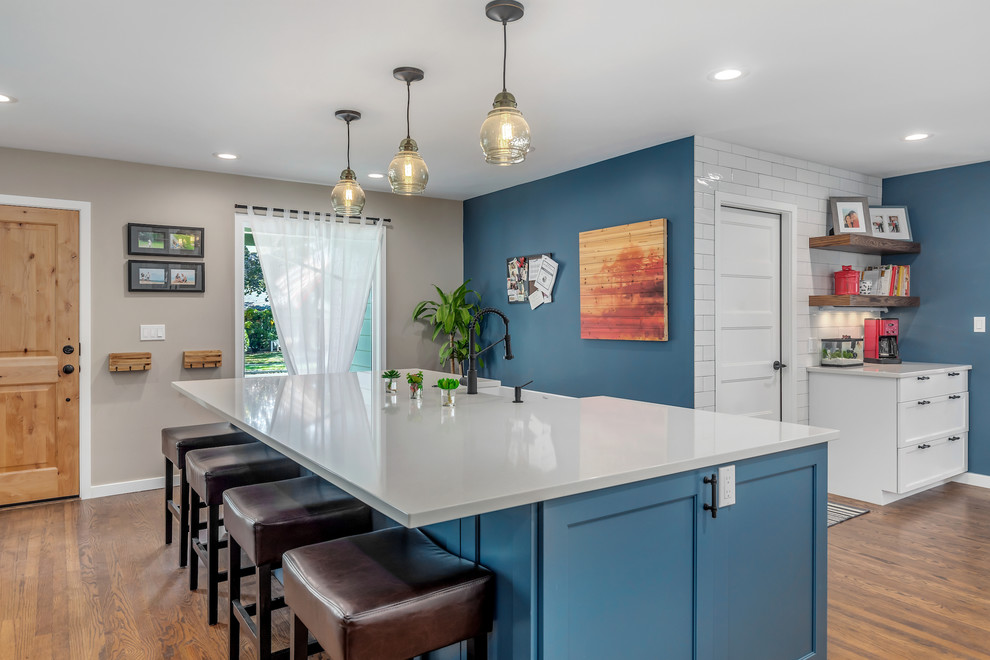 Large transitional l-shaped dark wood floor and brown floor eat-in kitchen photo in Portland with a farmhouse sink, recessed-panel cabinets, blue cabinets, quartz countertops, white backsplash, subway tile backsplash, stainless steel appliances, an island and white countertops