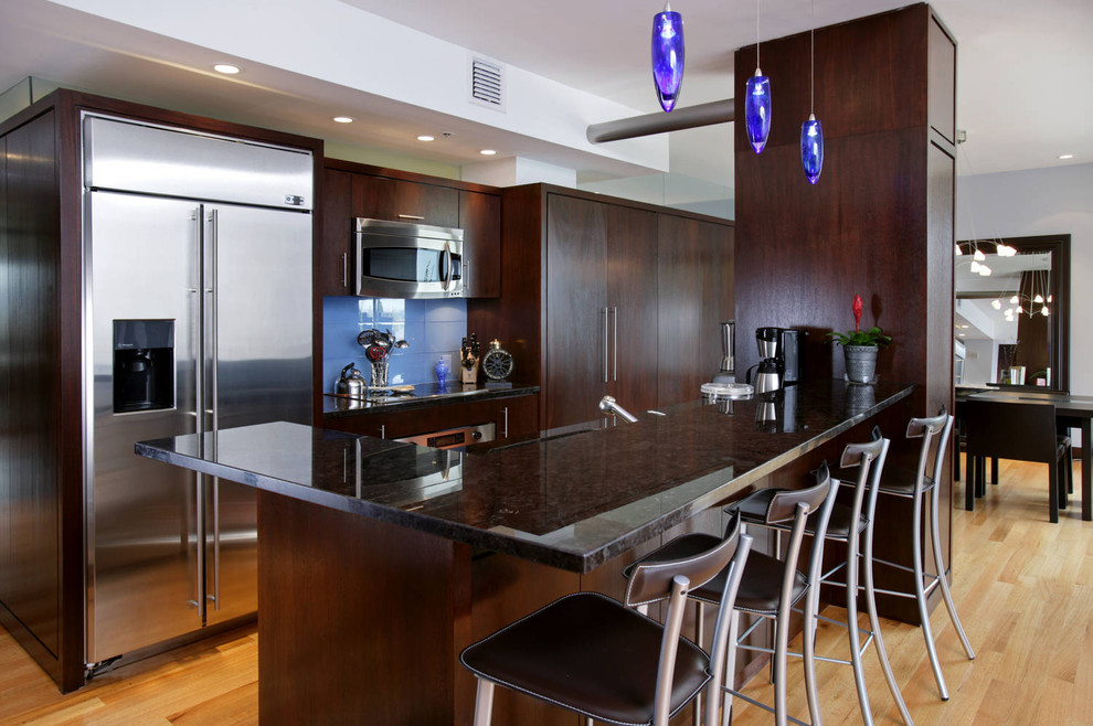 Kitchen - contemporary galley kitchen idea in Boston with flat-panel cabinets, dark wood cabinets, blue backsplash and stainless steel appliances