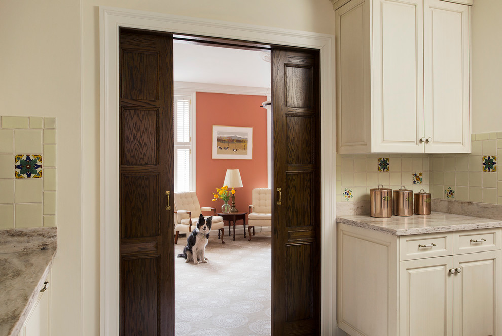 Inspiration for a large timeless l-shaped medium tone wood floor kitchen remodel in Boston with raised-panel cabinets, white cabinets, an undermount sink, quartzite countertops, beige backsplash, ceramic backsplash, stainless steel appliances and an island