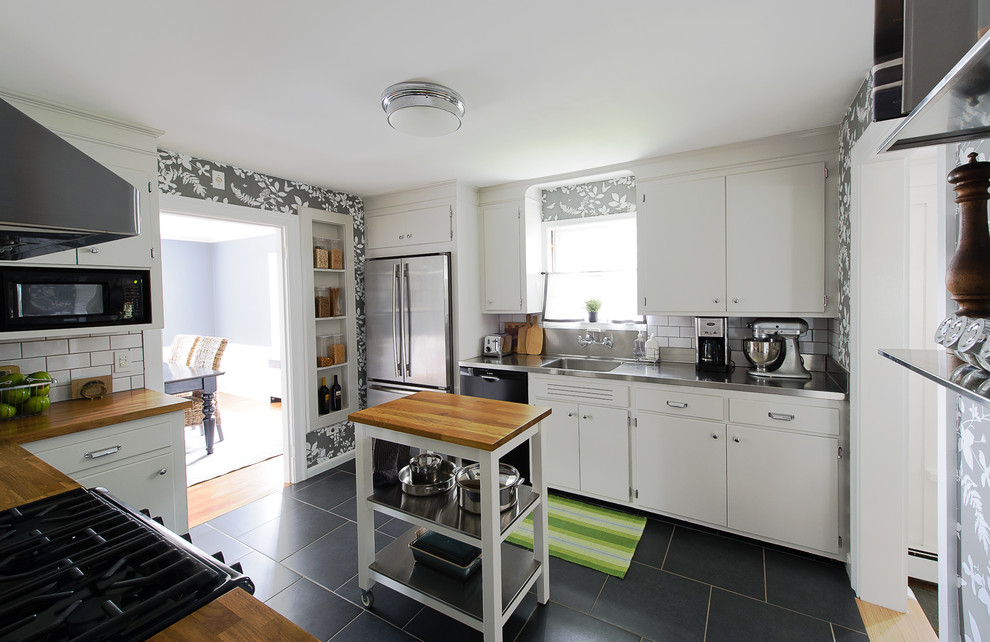 Example of a classic enclosed kitchen design in Boston with an integrated sink, flat-panel cabinets, white cabinets, stainless steel countertops, white backsplash, subway tile backsplash and stainless steel appliances