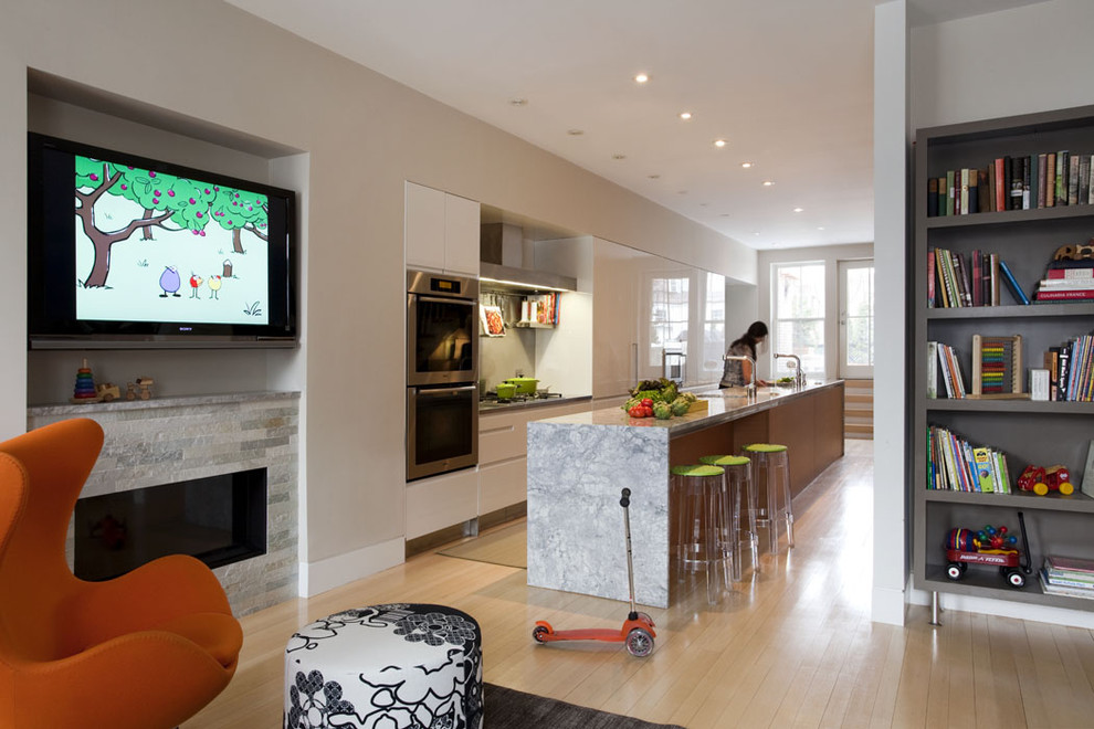 Eat-in kitchen - contemporary galley eat-in kitchen idea in Boston with flat-panel cabinets, marble countertops, stainless steel appliances and an island