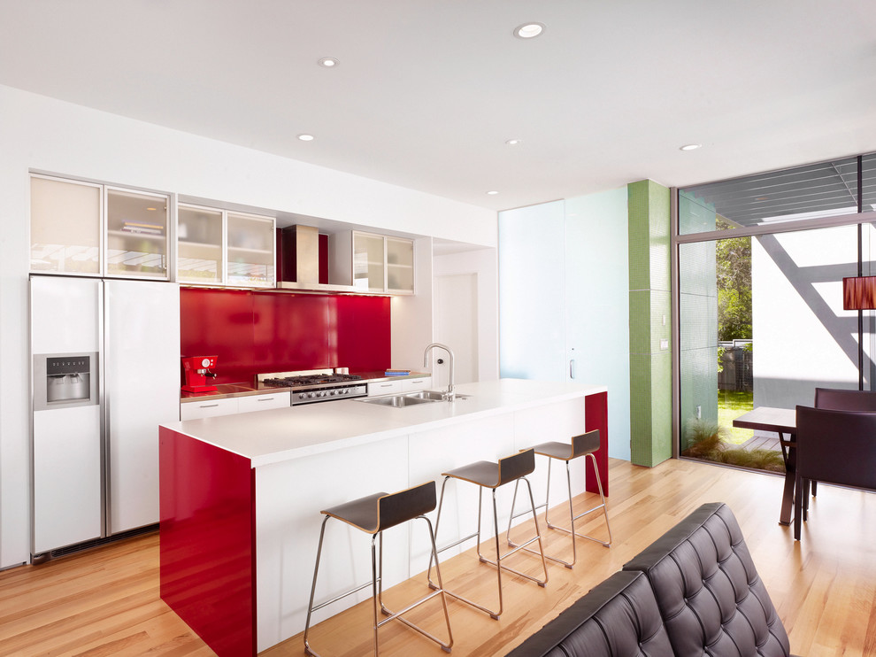 Open concept kitchen - modern galley open concept kitchen idea in Austin with glass-front cabinets, concrete countertops, a drop-in sink, red backsplash, metal backsplash and white appliances