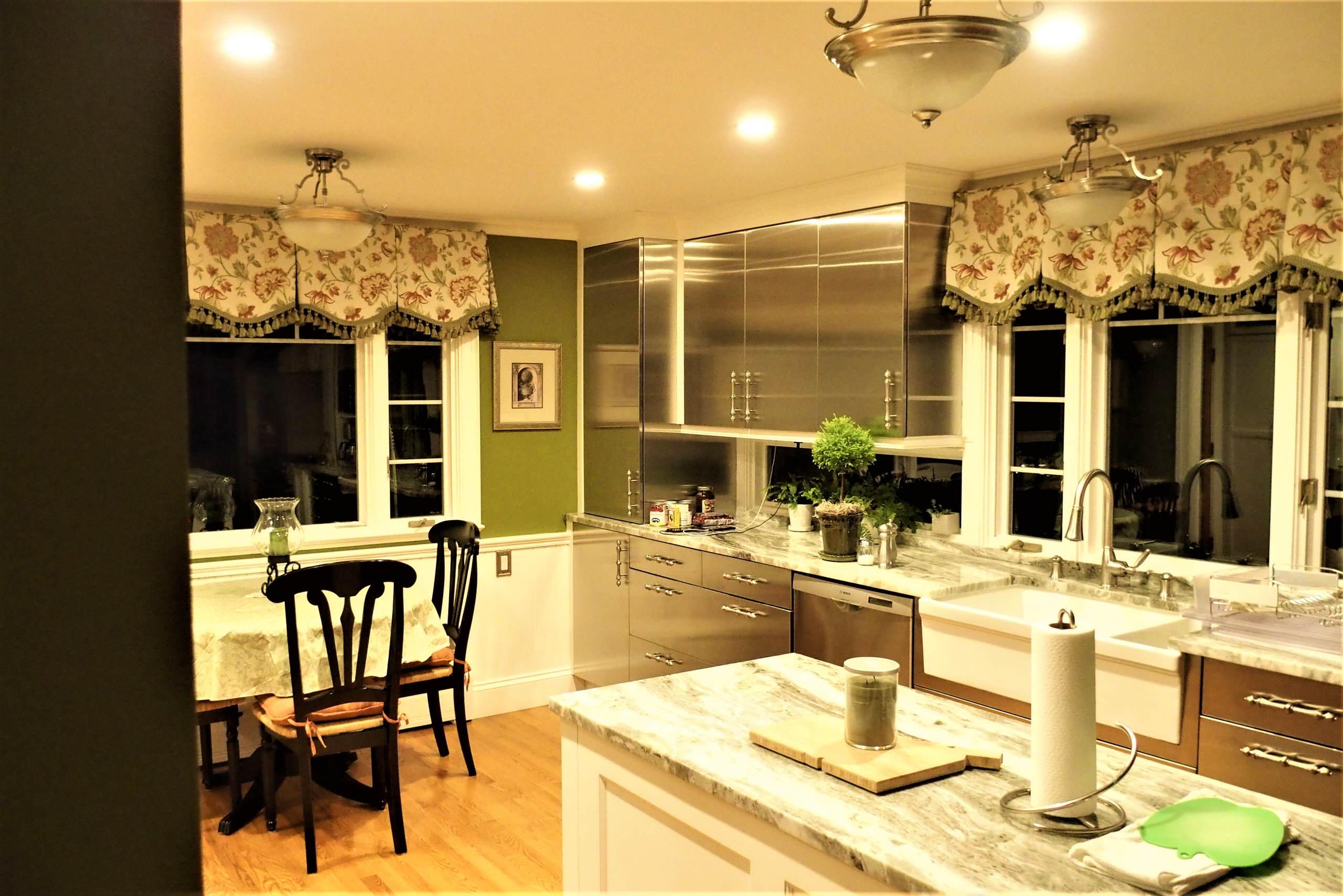 Box pleat valances with a shaped hem and tassel trim in a green kitchen