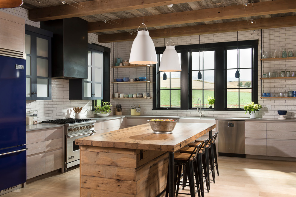 Example of a large cottage l-shaped light wood floor kitchen design in Other with a farmhouse sink, flat-panel cabinets, light wood cabinets, concrete countertops, white backsplash, subway tile backsplash, stainless steel appliances and an island