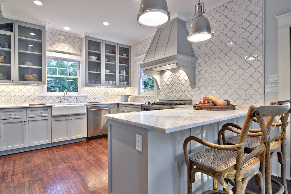 Example of a classic kitchen design in Austin with a farmhouse sink, shaker cabinets, gray cabinets, white backsplash, stainless steel appliances and marble countertops