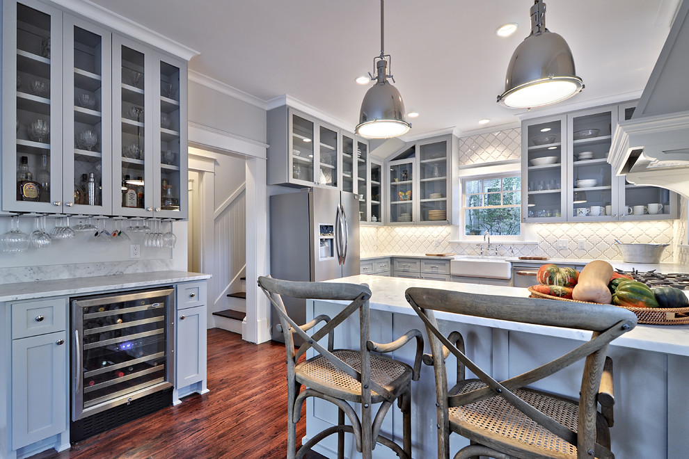 Example of a large classic dark wood floor kitchen design in Austin with a farmhouse sink, shaker cabinets, gray cabinets, marble countertops, white backsplash, stainless steel appliances and a peninsula