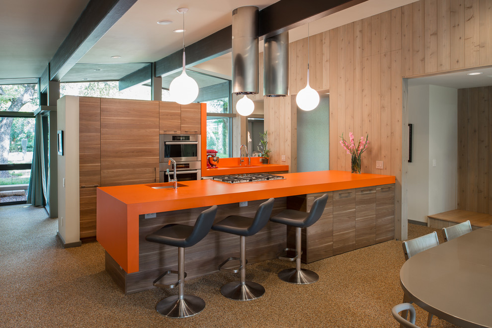 Mid-century modern galley eat-in kitchen photo in Austin with an undermount sink, flat-panel cabinets, medium tone wood cabinets, stainless steel appliances and orange countertops