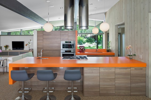 Mid-sized 1960s galley brown floor open concept kitchen photo in Austin with an undermount sink, flat-panel cabinets, medium tone wood cabinets, stainless steel appliances, an island, quartz countertops and orange countertops