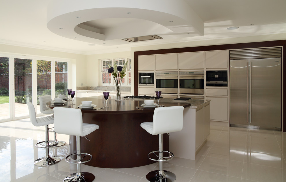 Inspiration for a large contemporary beige floor kitchen remodel in Hertfordshire with flat-panel cabinets, beige cabinets, stainless steel appliances and an island