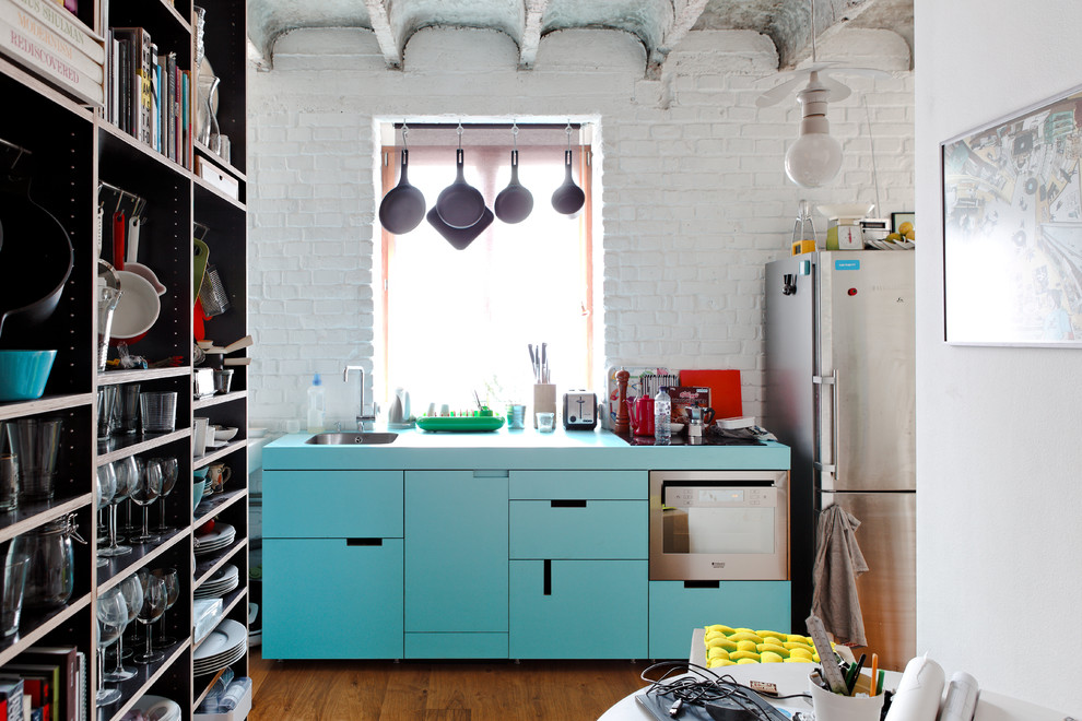 Urban single-wall kitchen photo with flat-panel cabinets, stainless steel appliances, turquoise cabinets and turquoise countertops