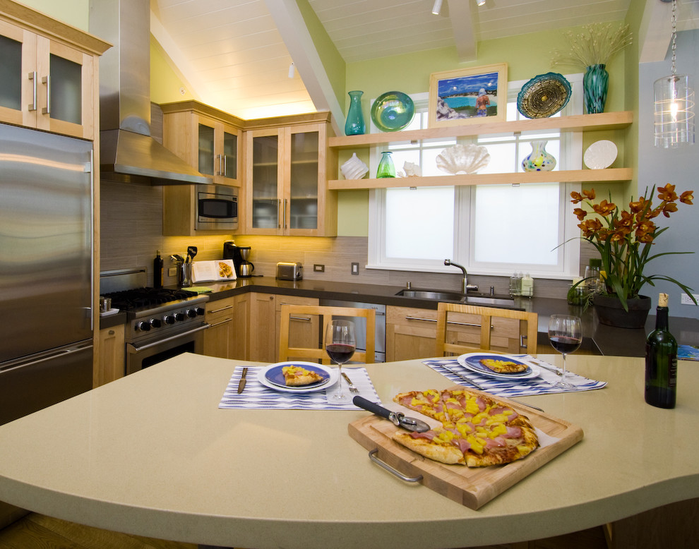 Trendy l-shaped kitchen photo in San Francisco with stainless steel appliances, quartz countertops, glass-front cabinets, light wood cabinets and beige backsplash
