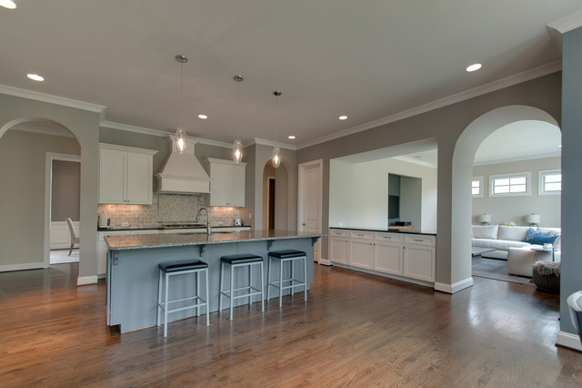 Example of a mid-sized 1960s dark wood floor and brown floor open concept kitchen design in Nashville with an undermount sink, recessed-panel cabinets, white cabinets, granite countertops, gray backsplash, marble backsplash, stainless steel appliances, an island and multicolored countertops